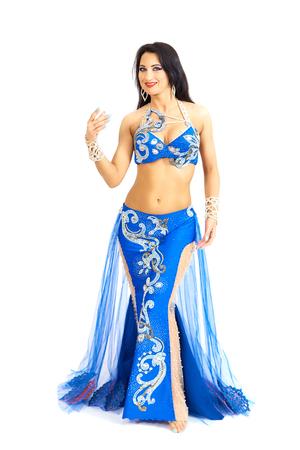 Eine junge Tänzerin in blauer Kleidung führt einen orientalischen Bauchtanz auf. Isolieren. Schönes Mädchen in der hellen nationalen Kleidung, die auf weißen Hintergrund tanzt.