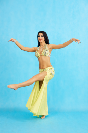 Charming dancer performs oriental belly dance on a blue background. A girl in a yellow dress is dancing an oriental belly dance on a blue background.