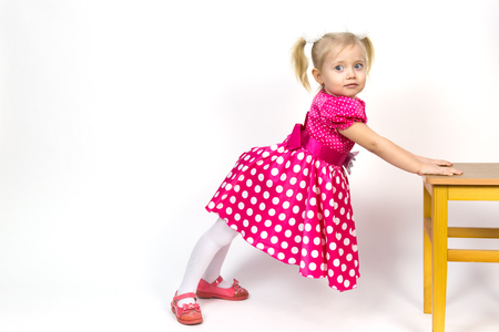 A beautiful young blond girl leans her elbows on a chair and puts her head on her hands. Little girl 3 years old on a white background put her head on her hands.