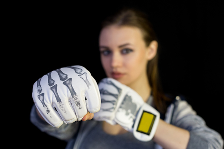 Girl sportswoman in gloves for boxing on a black background. The girl is a fighter of mixed martial arts who covers her face with gloves from blows.