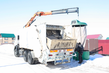 Garbage collection from yard territories by the machine manipulator. The machine collects containers with household garbage.