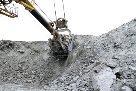 The excavator rakes a bunch of stones in the quarry. The bucket of the excavator cuts into a mountain of stones.