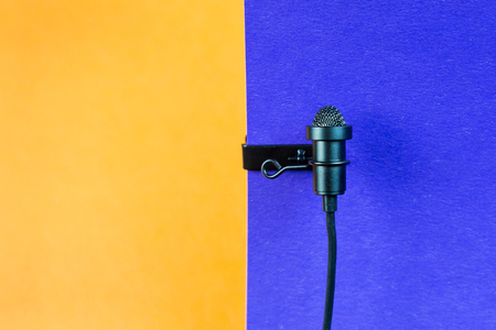Miniature microphone of the buttonhole. A small microphone for recording quality sound on a blue background. Stock Photo