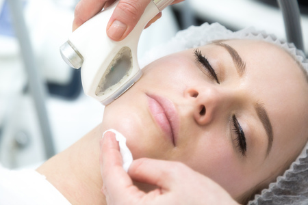 Removing wrinkles on the face and neck with massage. A beautiful blonde smooths wrinkles on the face and neck area with the help of massage in the beauty salon.