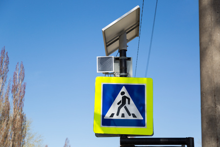 The traffic light works from the solar battery. At the pedestrian crossing a modern traffic light is installed which uses solar energy. Stock Photo