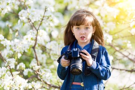 Une petite fille prend des photos de fleurs dans un verger de pommiers à l & # 39 ; extrémité d & # 39 ; une petite fille. prend des photos d & # 39 ; une robe d & # 39 ; été dans un peu de fleurs Banque d'images - 102031124