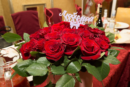 A bouquet of flowers for my mother. The inscription on the bouquet is To my beloved mother. A huge bouquet of beautiful red roses in a box as a gift for parents.