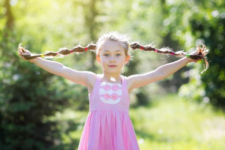 Little girl with long braids hair. A girl in a red dress holding her hair braided in pigtails with her hands.