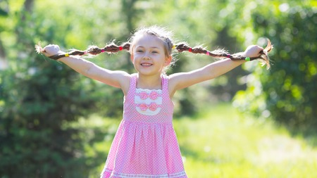 A girl with long braids made of hair. Little girl is holding herself by the hair in the city park.