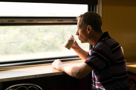 A man is riding in a train restaurant. A man 40 - 50 years old is drinking tea in a long-distance train.