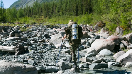 A man with a backpack on his shoulders. A tourist walks along the mountain river in the Republic of Altai, Russia.