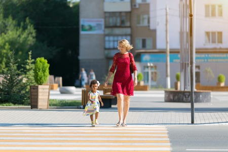 The child runs away from the mother on the pedestrian crossing. A black girl runs along the road from her mother, a danger.