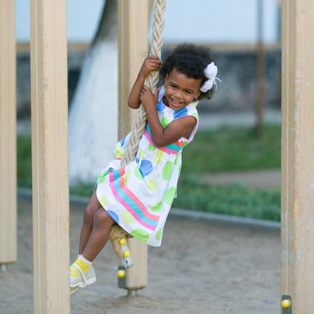 The girl is hanging on the sports rings. African American girl plays on a sports playground.