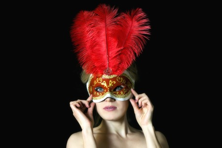 The girl European appearance in the carnival mask. A blond woman in a beautiful mask with feathers on a black background.