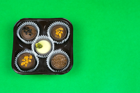Five chocolates on a colored background. Candy with different fillings in a package of 5 pieces.