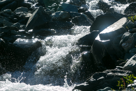 A fast mountain stream in the mountains. Clean drinking water in a mountain stream at dawn.