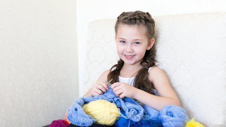 A girl with a mobile phone on the couch. There are threads for knitting in different colors. Imagens
