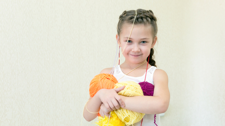 A girl with balls of thread for knitting. The little girl holds up her hands.