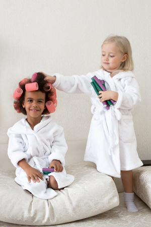 Little girls play with hair curlers and hairpins. Girls of different nationalities. 스톡 콘텐츠