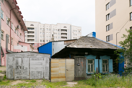 Old destroyed house among the new houses. Slums hut is poor among new buildings and skyscrapers.