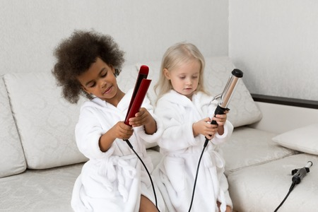 Small children play with curling irons. Girls in white coats, Caucasian and African American play and consider electric hair curlers.