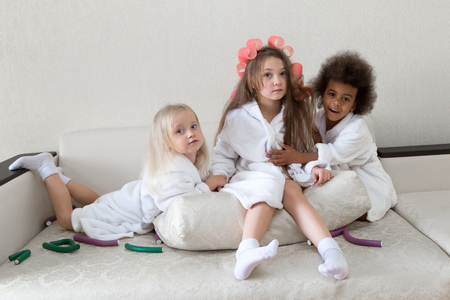 Three sisters hug sitting on the couch. Girls girlfriend 5 years of age in white coats