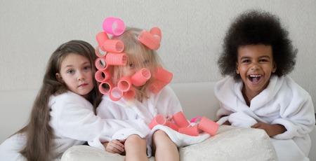 Little girls twirl hair curlers.