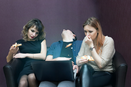 The girls watch a television series and the man fell asleep from boredom. Imagens