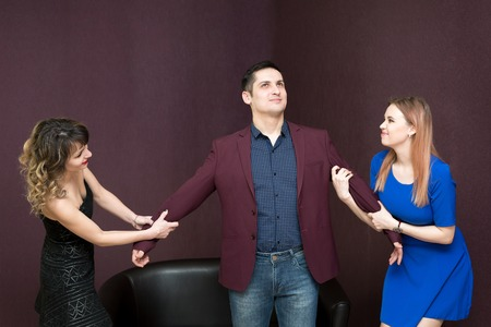 Two girls pull a man in different directions, whose husband is he.