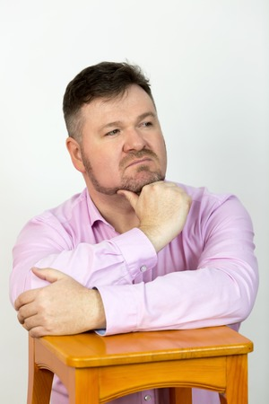 Male 40-45 years old in a pink shirt with a beard on a white background.