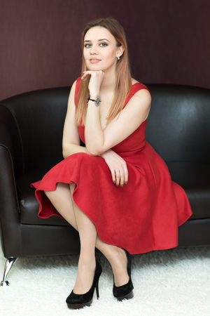 A woman in a red dress with a big magnificent breast is sitting on the sofa. Stock Photo