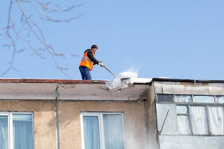 City Yasny, RUSSIA, February 20, 2019. Worker cleans the roof of a multistory building. Editorial. A man with a shovel removes a residential building. Editorial.