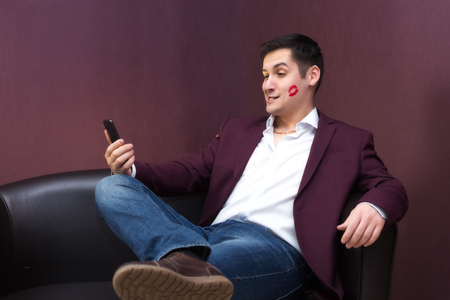 A man with lipstick on a cheek kiss. Young playboy lover with lipstick makes a photo on a smartphone 版權商用圖片