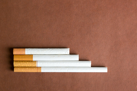 Cigarettes of different lengths on a dark background. Cigarettes of different sizes on a brown background. Фото со стока