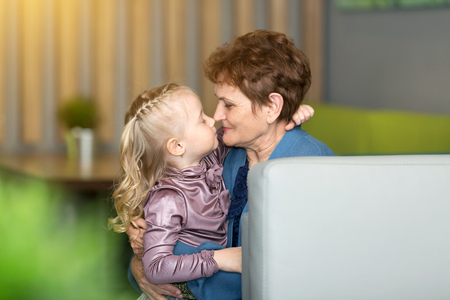 Little granddaughter tightly hugs her grandmother. A girl of 4-5 years old, hugging her old grandmothers pensioner in a cafe.