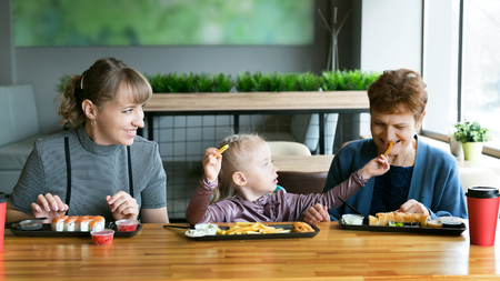 Women of the same family Grandmother, daughter, granddaughter eat in a cafe. Family dinner generation of women.,