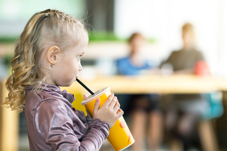 His girlfriend drinks juice A small child alone drinking water. A child without supervision, indifference of parents.,