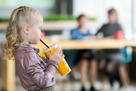 His girlfriend drinks juice A small child alone drinking drinks. A child without supervision, indifference of parents.