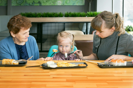 Mom and grandmother feed the little girl together. But it is not a problem.