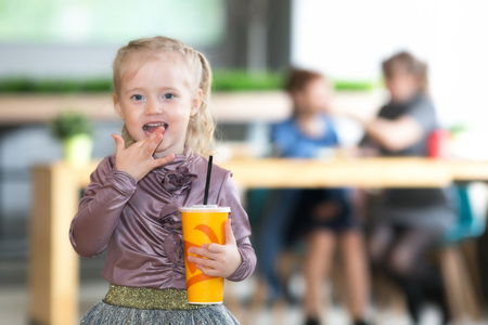 His girlfriend drinks juice A small child alone drinking water. A child without supervision, indifference of parents 写真素材