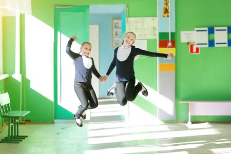 Two schoolgirls jump in the corridor holding hands. Schoolgirl girls jumping at school recess. 版權商用圖片