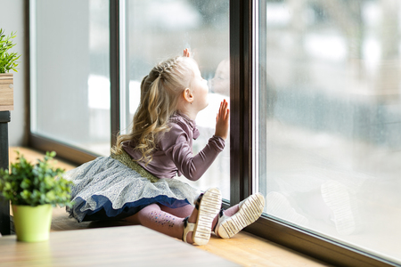 A beautiful child is sitting near a large window. A little girl, 4-5 years old sitting in the cafe.