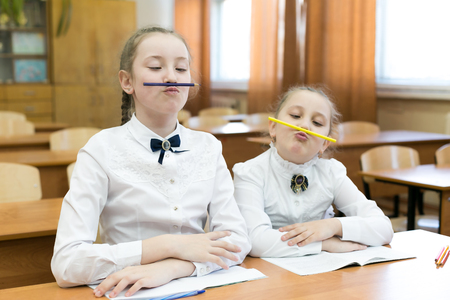 Children indulge in school in the classroom make face mimicry. Make up funny facial expression. Stock Photo