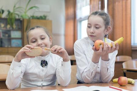 Schoolgirl with fruit in her hands envies classmate with meal of cheese and meat.