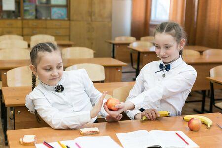 Schulmädchen behandelt ihrer Freundin einen roten Apfel. Ein Mädchen gibt einen vegetarischen Apfel.