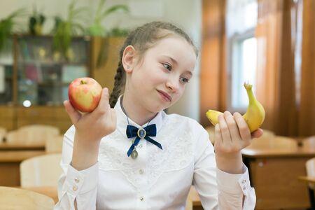 Chica en uniforme escolar elige comida para el almuerzo. Te hace un bocadillo saludable. Foto de archivo