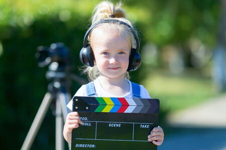 Portrait of a child with a TV clapper. Television numerator. A little girl is in headphones with a TV in her hands.