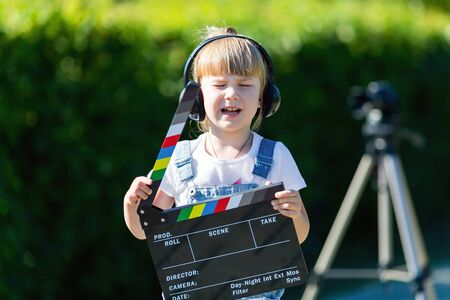 Portrait of a child with a TV clapper. A little girl in headphones with a TV in her head.