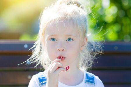 Een klein meisje zuigt een grote zoete snoep terwijl ze op een bankje zit. Fontein.