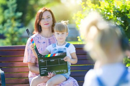A little girl in headphones with a camera shoots the plot. Child blogger shoots mom Children prepare a video story, news for social networks.